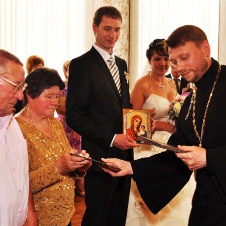 священник Андрей Крылов вручает иконы семейным парам.